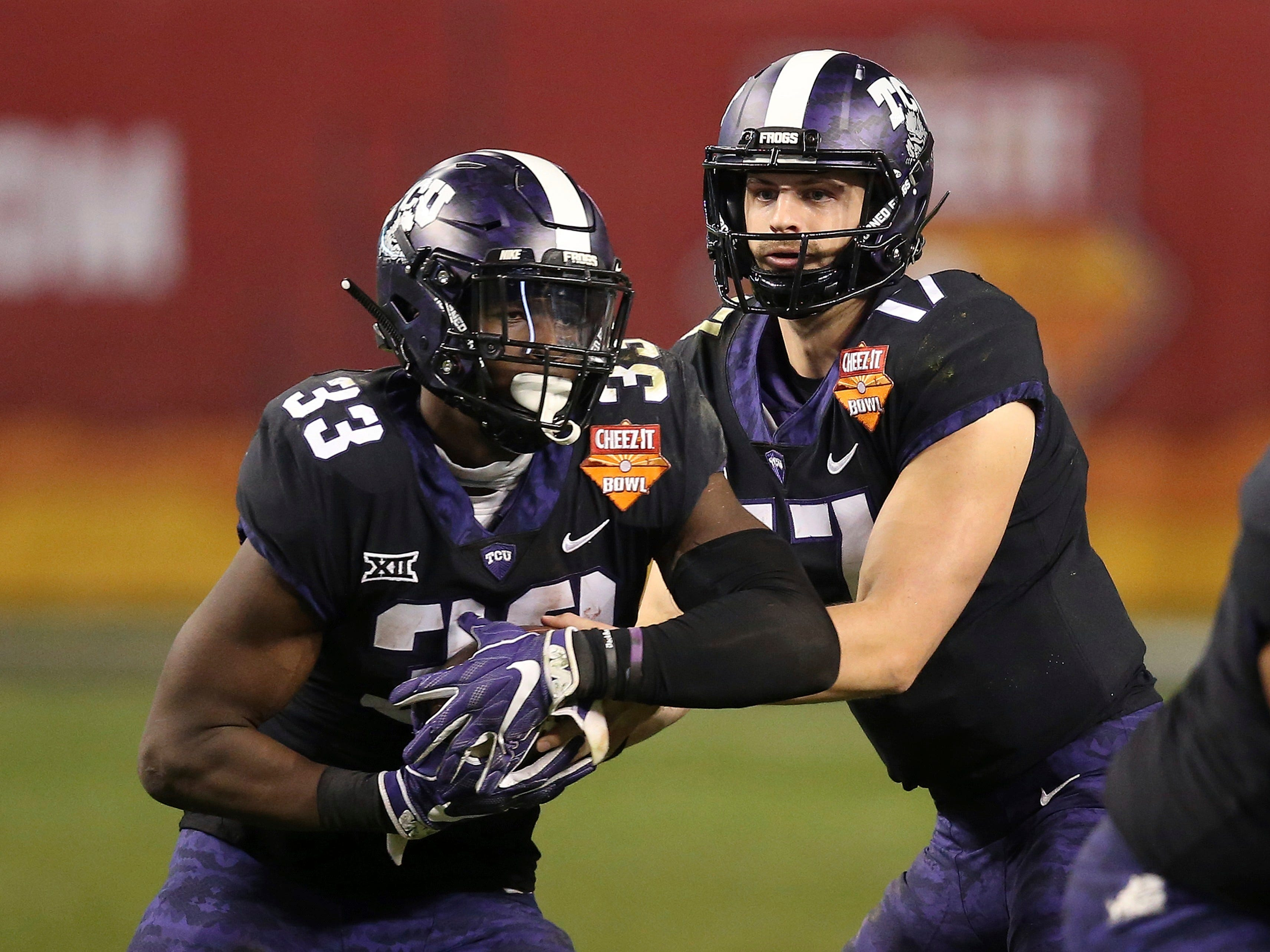 TCU running back Sewo Olonilua (33) takes a handoff from quarterback Grayson Muehlstein (17) during the second half of the Cheez-It Bowl NCAA college football game against California Thursday, Dec. 27, 2018, in Phoenix. TCU defeated California 10-7 in overtime.