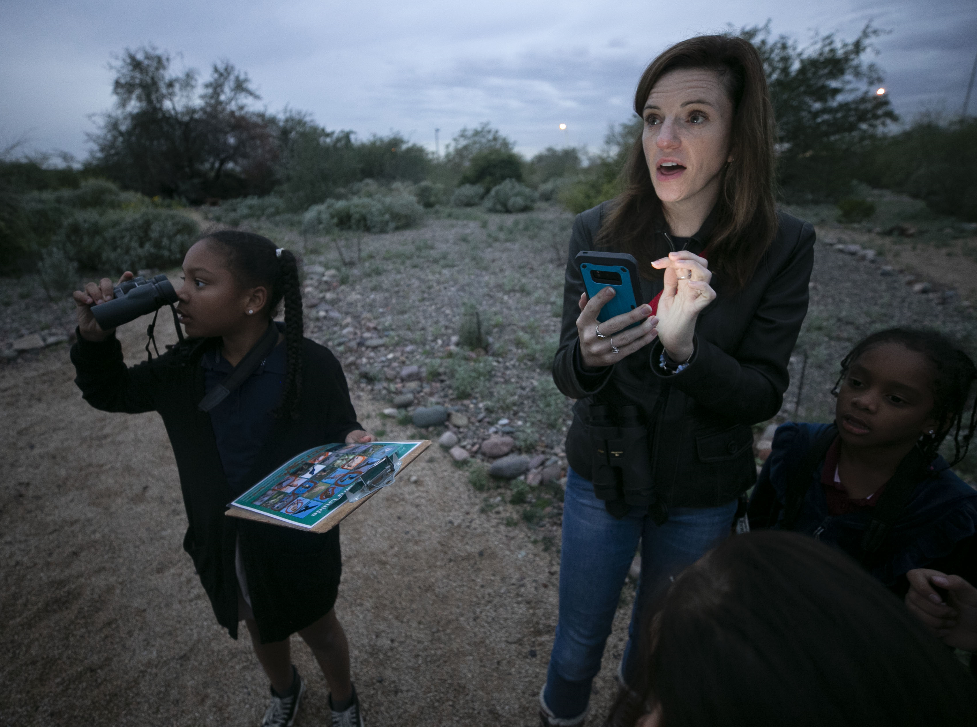 Emily Martell, a teacher/naturalist with the Nina Mason Pulliam Rio Salado Audubon Center, plays audio of a bird call from her phone while bird-watching with kids from the Tri-City West Thornwood Branch of Avondale of the Boys & Girls Clubs of Metro Phoenix, on Dec. 6, 2018.