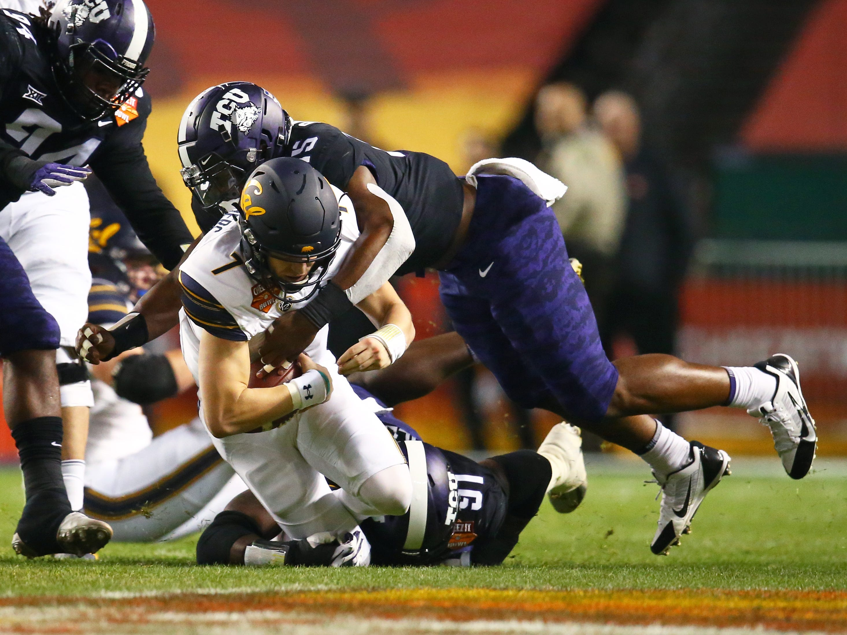 Dec 26, 2018; Phoenix, AZ, USA; California Golden Bears quarterback Chase Garbers (7) is tackled by Texas Christian Horned Frogs defensive end Ben Banogu (15) in the first half of the 2018 Cheez-It Bowl at Chase Field.