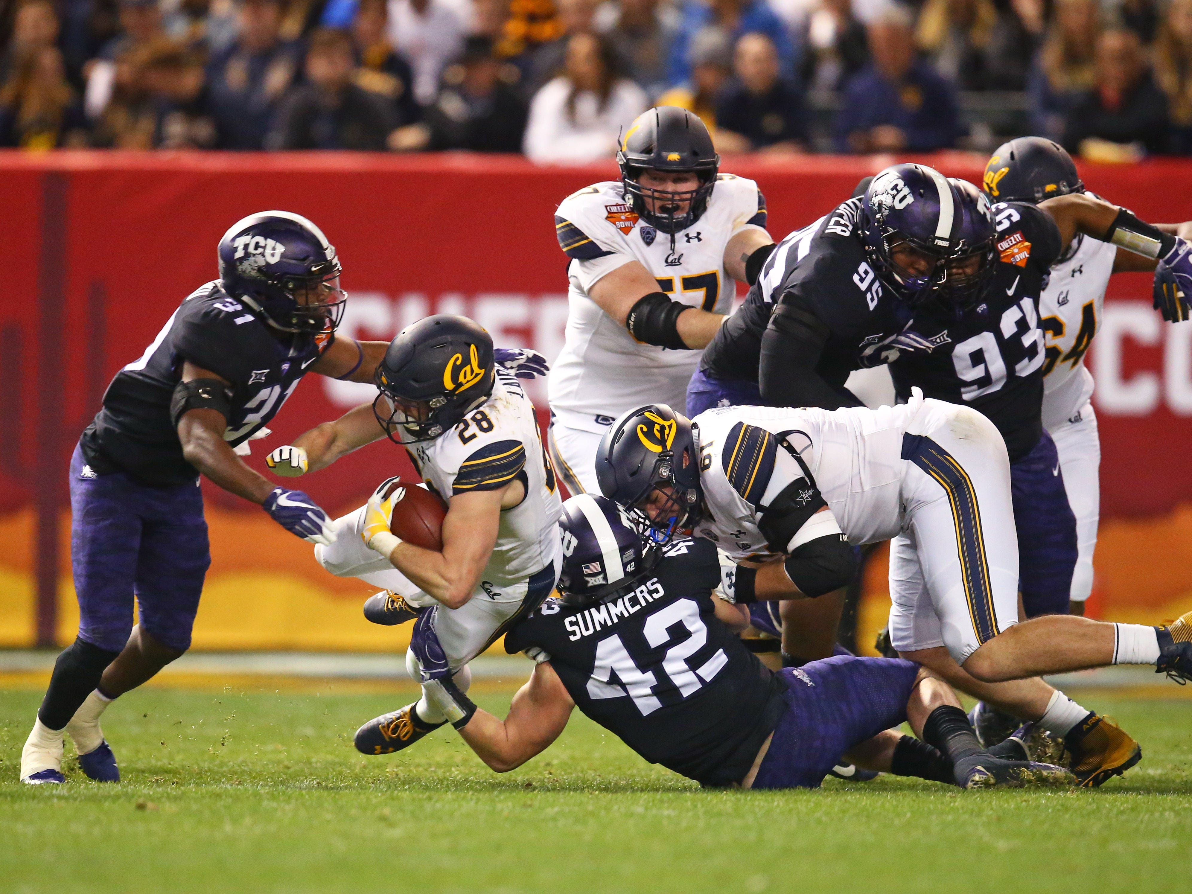Dec 26, 2018; Phoenix, AZ, USA; California Golden Bears running back Patrick Laird (28) is tackled by Texas Christian Horned Frogs linebacker Ty Summers (42) and safety Ridwan Issahaku (31) in the first half of the 2018 Cheez-It Bowl at Chase Field.
