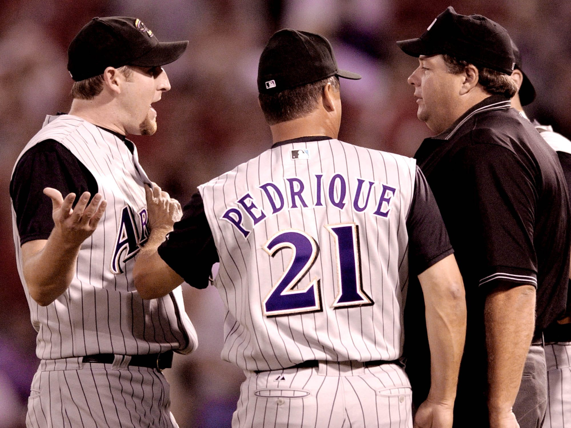 Arizona Diamondbacks starting pitcher Brandon Webb, left, is held back by his manager Al Pedrique during an arguement with home plate umpire Jerry Layne after Webb threw at St. Louis Woody Williams while he was at bat in the third inning in St. Louis,  Friday, Sept. 17, 2004. Webb was ejected and Pedrique was later ejected later in the third for arguing with the umpire.(AP Photo/James A. Finley)