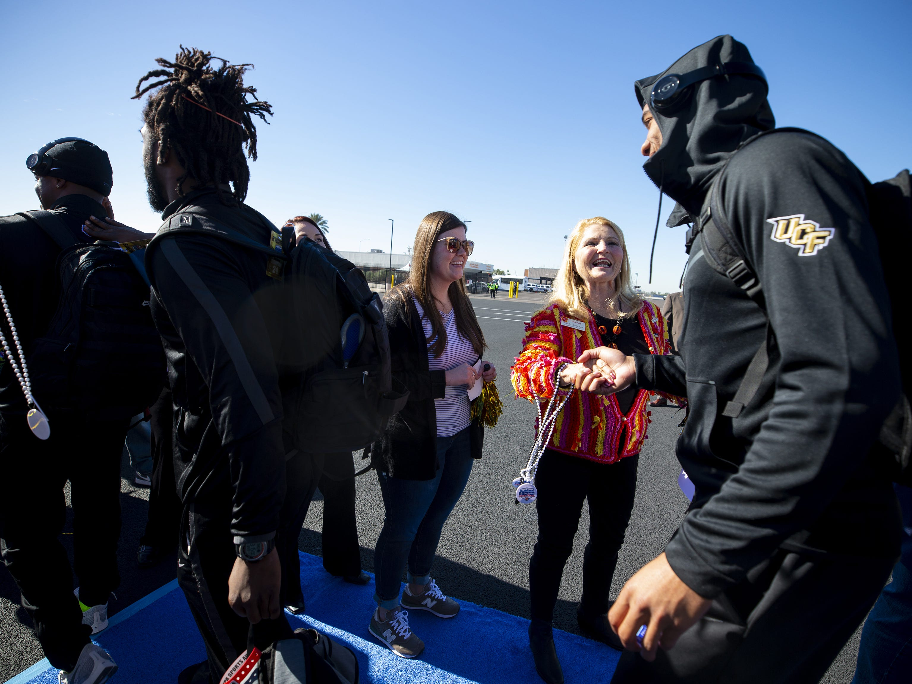 Fiesta Bowl ambassador Dennice Dunaway greets players from the Central Florida football team at Sky Harbor International Airport in Phoenix on December 27. Central Florida will face LSU in the Fiesta Bowl on New Year's Day.