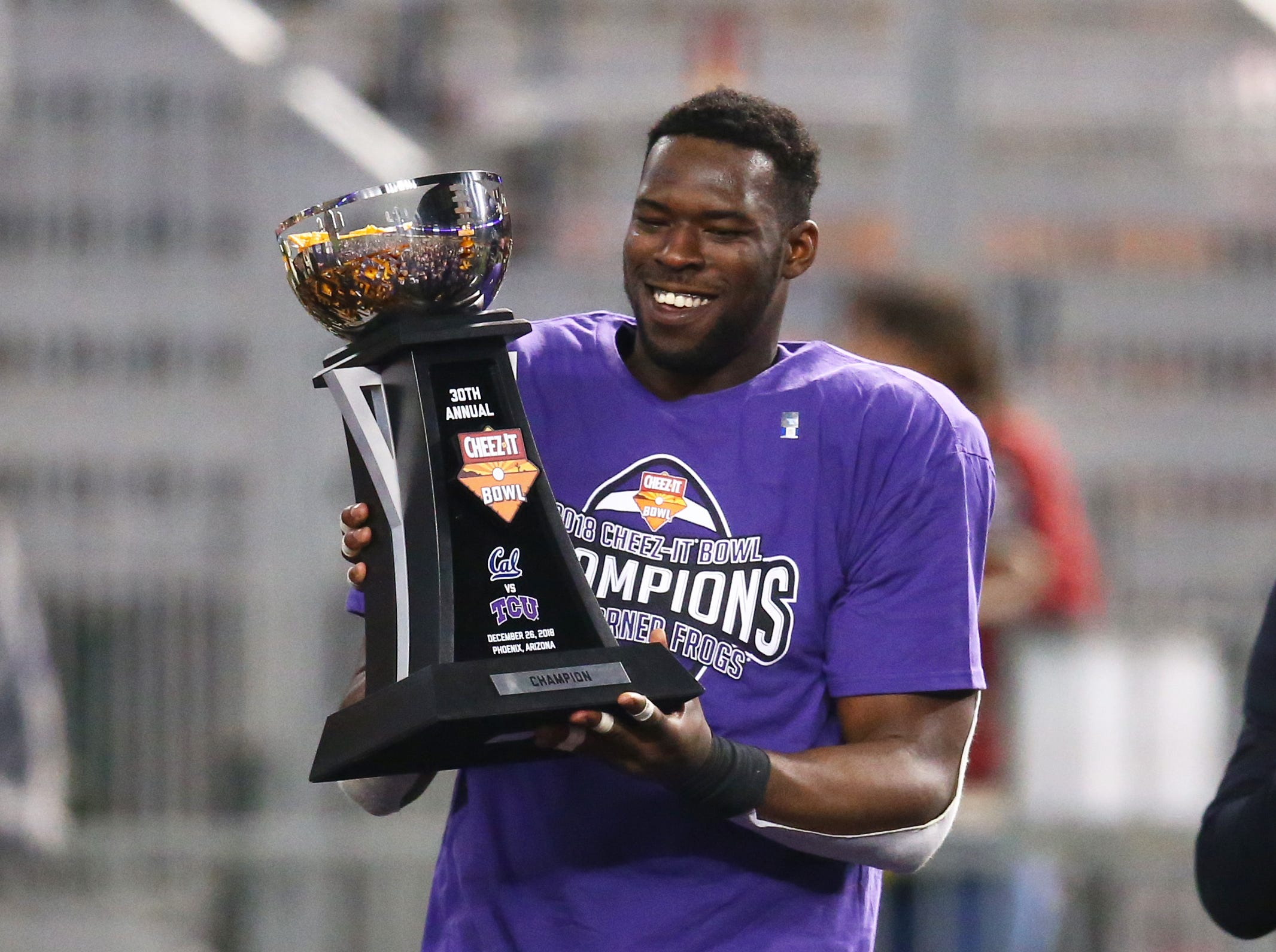 Dec 26, 2018; Phoenix, AZ, USA; Texas Christian Horned Frogs defensive end Ben Banogu celebrates with the trophy after defeating the California Golden Bears in overtime of the 2018 Cheez-It Bowl at Chase Field. Mandatory Credit: Mark J. Rebilas-USA TODAY Sports