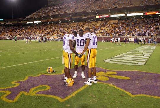 LSU players Ronnie Prude, Joseph Addai and Bennie Brazell (left to right) pray on a Louisiana outline on the field after the Tigers' 35-31 victory over Arizona State at Sun Devil Stadium.