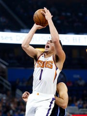 Dec 26, 2018; Orlando, FL, USA;  Phoenix Suns guard Devin Booker (1) shoots the ball against Orlando Magic guard Evan Fournier (10)  for the foul during the first quarter at Amway Center.