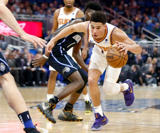 Dec 26, 2018; Orlando, FL, USA; Phoenix Suns guard Devin Booker (1) drives through the lane past Orlando Magic forward Jonathan Isaac (left center) during the first quarter at Amway Center.