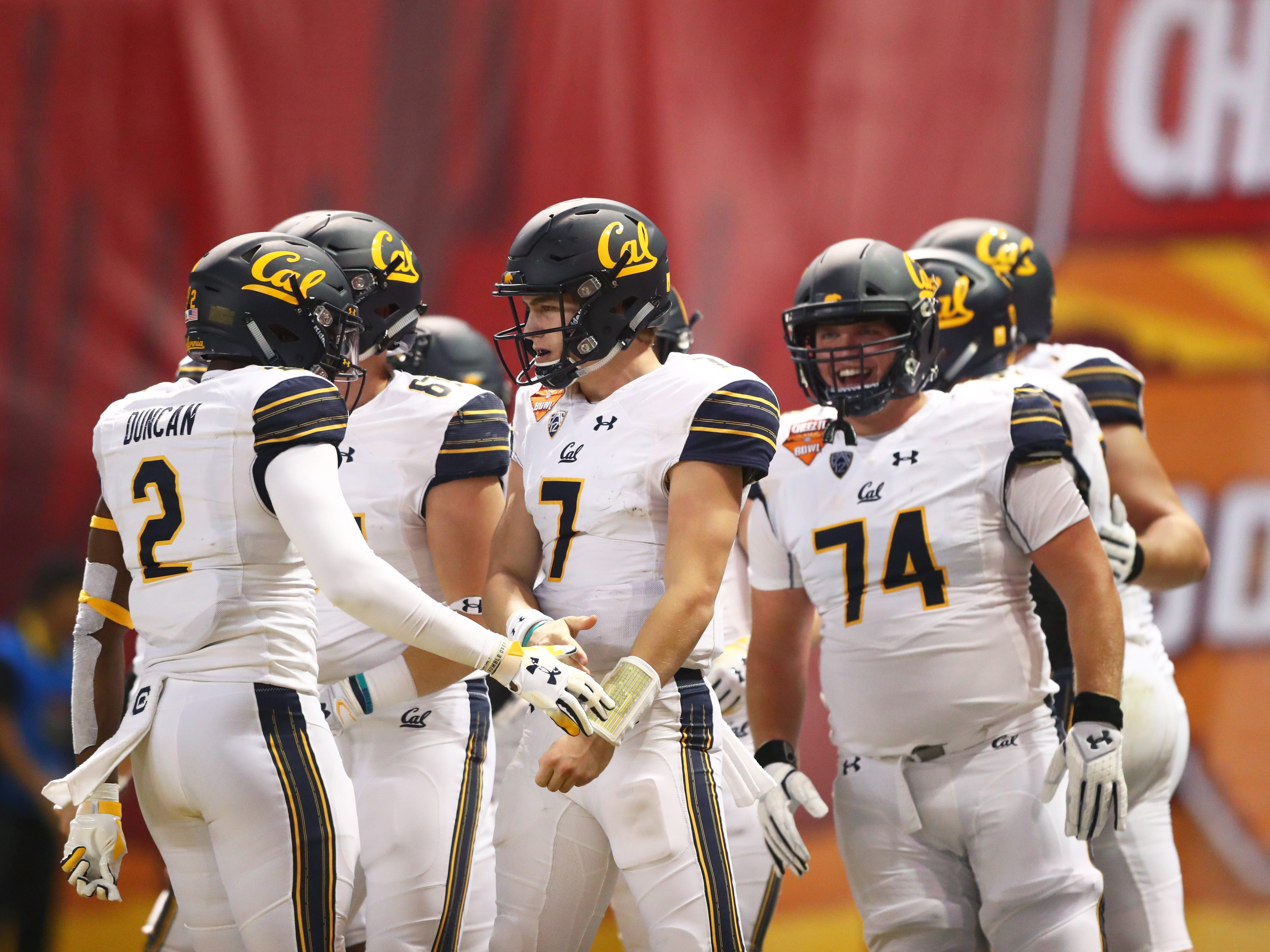 Dec 26, 2018; Phoenix, AZ, USA; California Golden Bears quarterback Chase Garbers (7) celebrates with teammates after scoring a touchdown against the Texas Christian Horned Frogs in the first quarter of the 2018 Cheez-It Bowl at Chase Field.