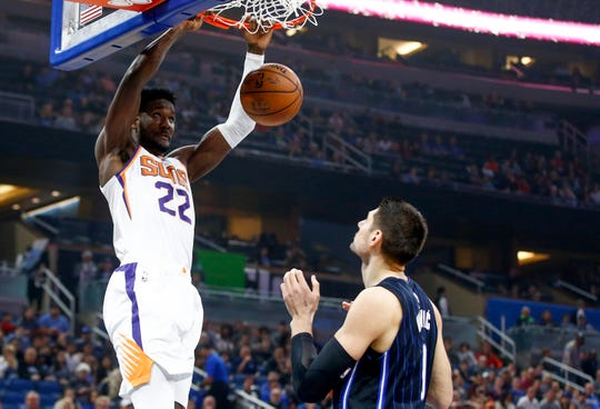 Dec 26, 2018; Orlando, FL, USA; Orlando Magic center Nikola Vucevic (9) watches as Phoenix Suns center Deandre Ayton (22) dunks the ball during the first quarter at Amway Center.