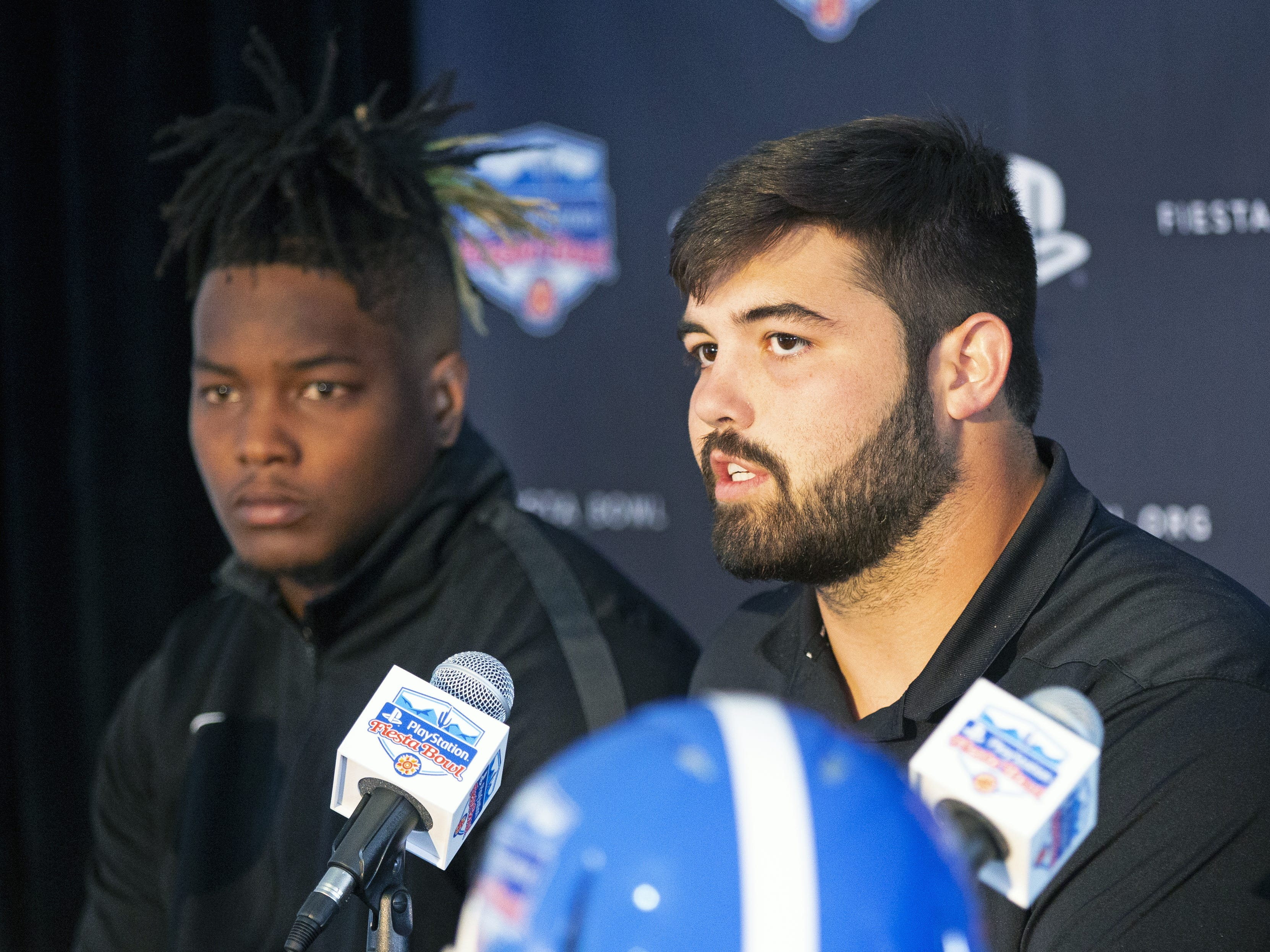 Central Florida defensive lineman, Titus Davis, left, and offensive lineman, Wyatt Miller, speak to the media after arriving at Sky Harbor International Airport in Phoenix on December 27. Central Florida will face LSU in the Fiesta Bowl on New Year's Day.