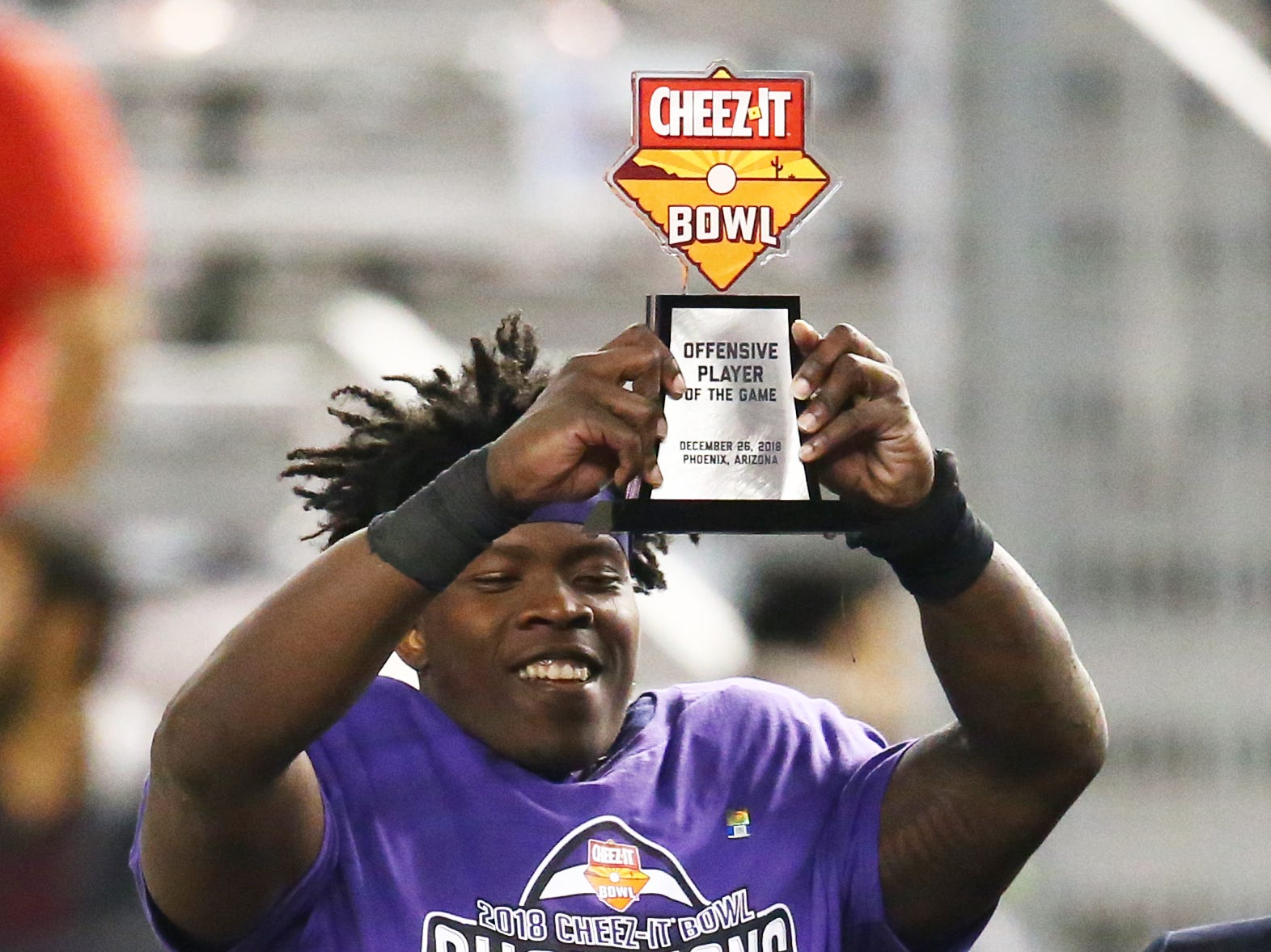 Dec 26, 2018; Phoenix, AZ, USA; Texas Christian Horned Frogs running back Sewo Olonilua celebrates with the offensive MVP trophy after defeating the California Golden Bears in overtime of the 2018 Cheez-It Bowl at Chase Field. Mandatory Credit: