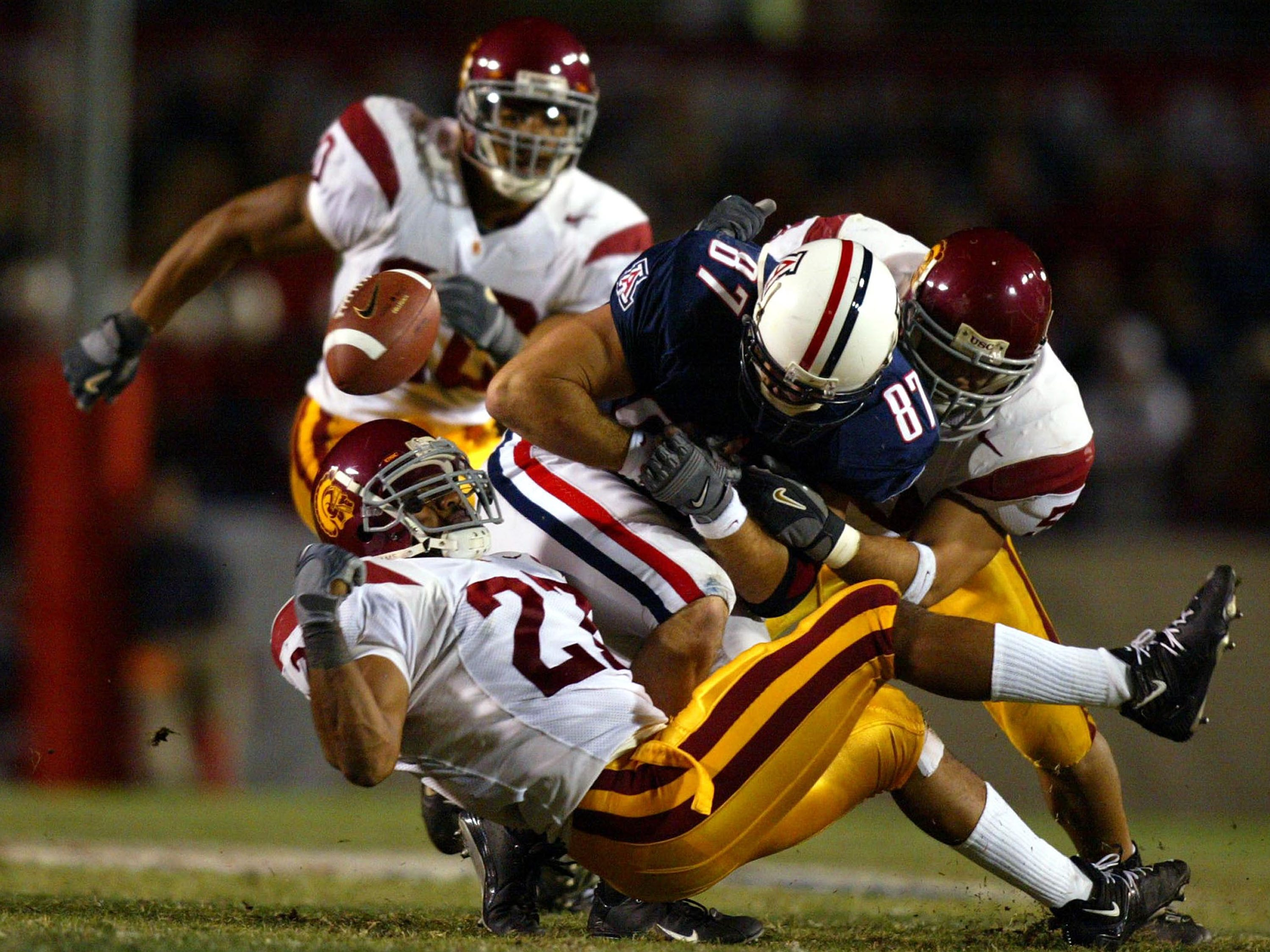 TUCSON, AZ - NOVEMBER 15:  Jason Leach #27 of the USC Trojans causes the fumble by Steve Flemming #87 of the Arizona Wildcats during the 2nd period of their game at Arizona Stadium on November 15, 2003 in Tucson, Arizona.