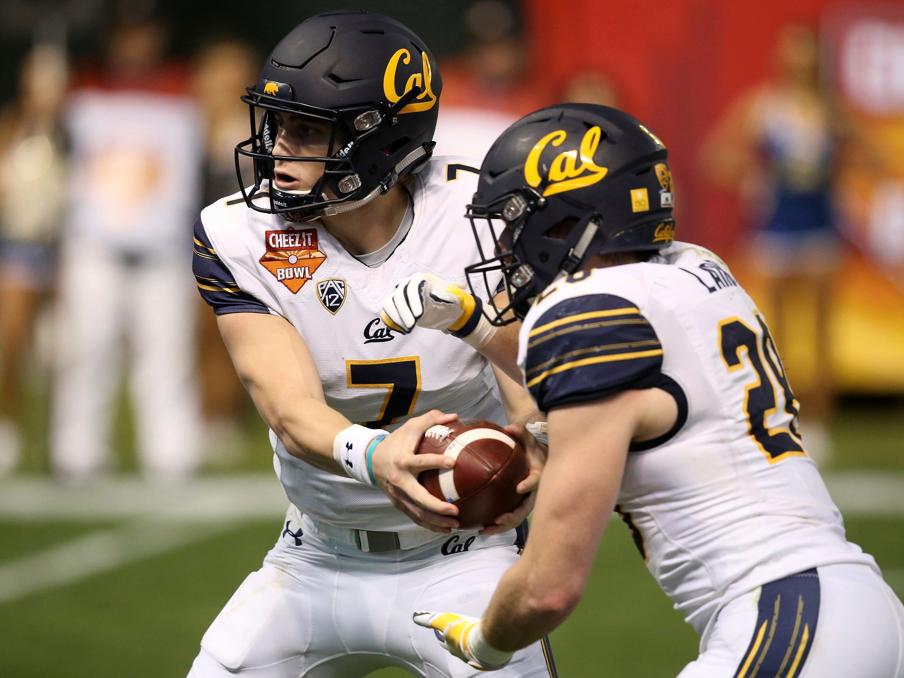 California quarterback Chase Garbers (7) hands the ball off to running back Patrick Laird (28) during the first half of the Cheez-It Bowl NCAA college football game against TCU on Wednesday, Dec. 26, 2018, in Phoenix.