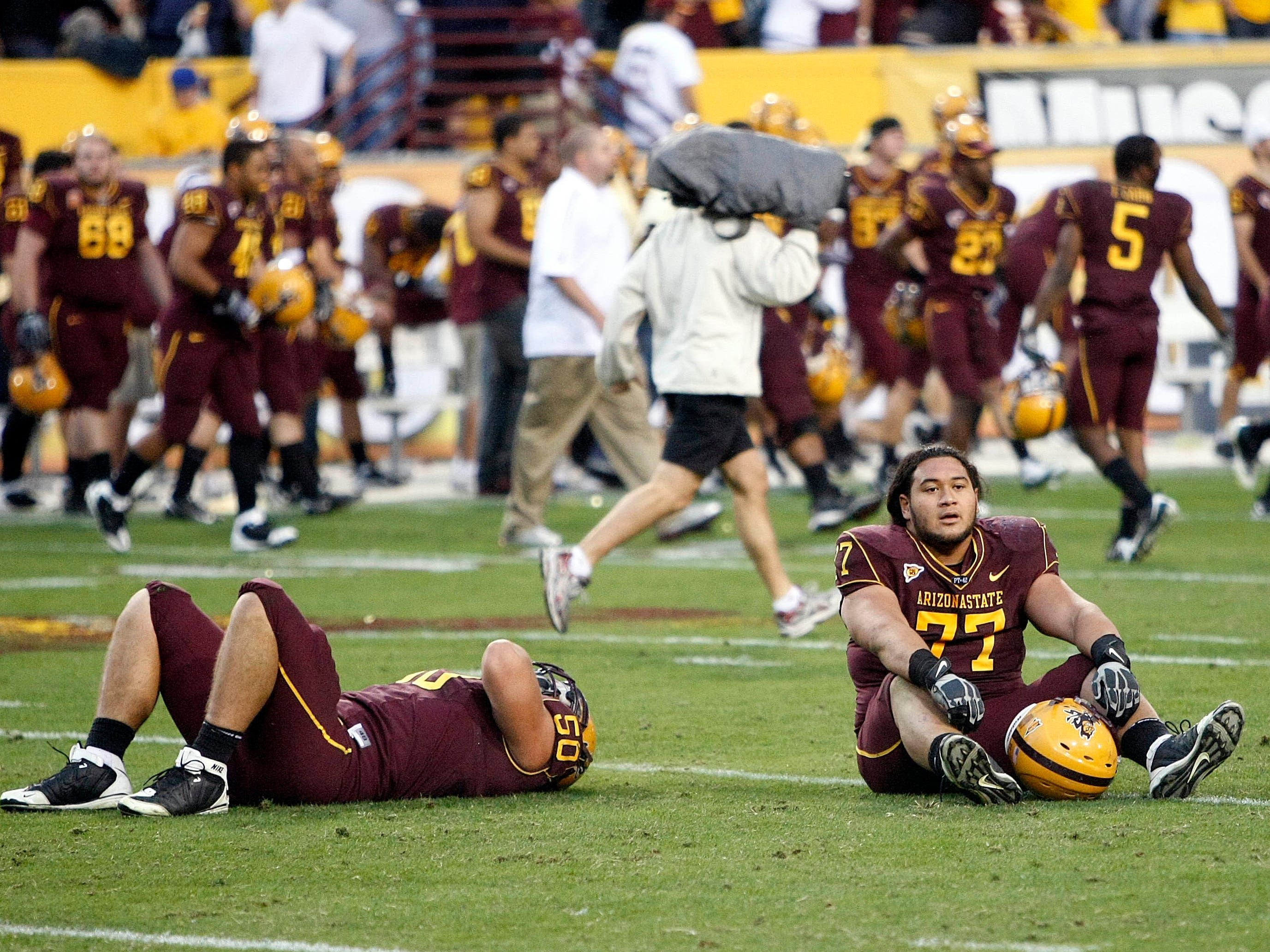 Arizona State's Lawrence Guy, left, and Saia Falahola sit on the field after losing an NCAA college football game against Arizona, Saturday, Nov. 28, 2009, in Tempe, Ariz. Arizona won 20-17. (AP Photo/Matt York)