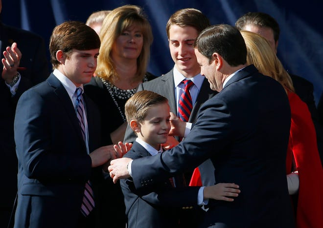 Shortly after being sworn in, Arizona Gov. Doug Ducey gets a hug from son Sam Ducey as sons Joe Ducey (left) and Jack Ducey (second from right) look on during inauguration ceremonies at the Arizona Capitol on Jan. 5, 2015, in Phoenix.
