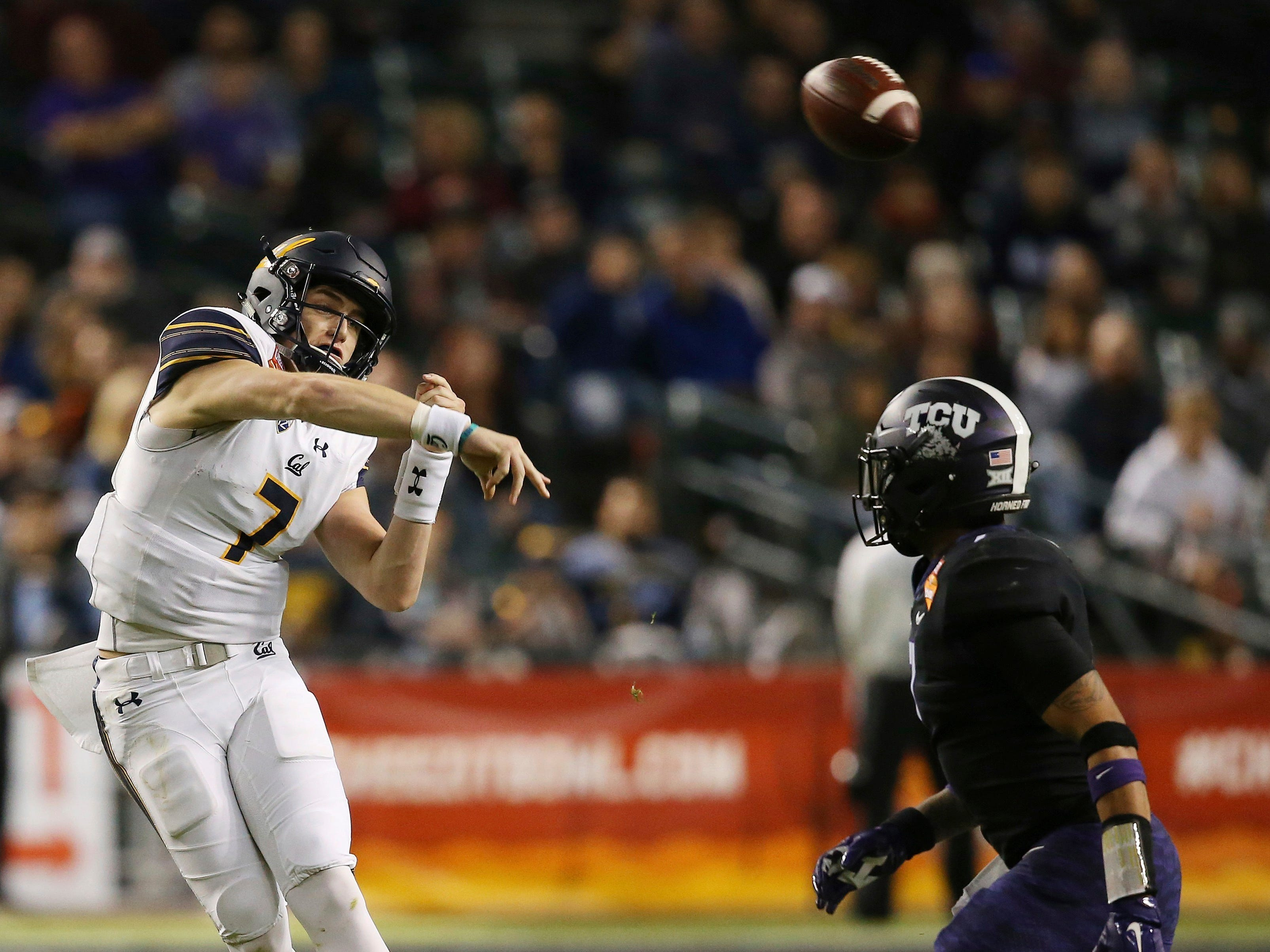 California quarterback Chase Garbers (7) throws a pass over TCU linebacker Arico Evans, right, during the first half of the Cheez-It Bowl NCAA college football game Wednesday, Dec. 26, 2018, in Phoenix.