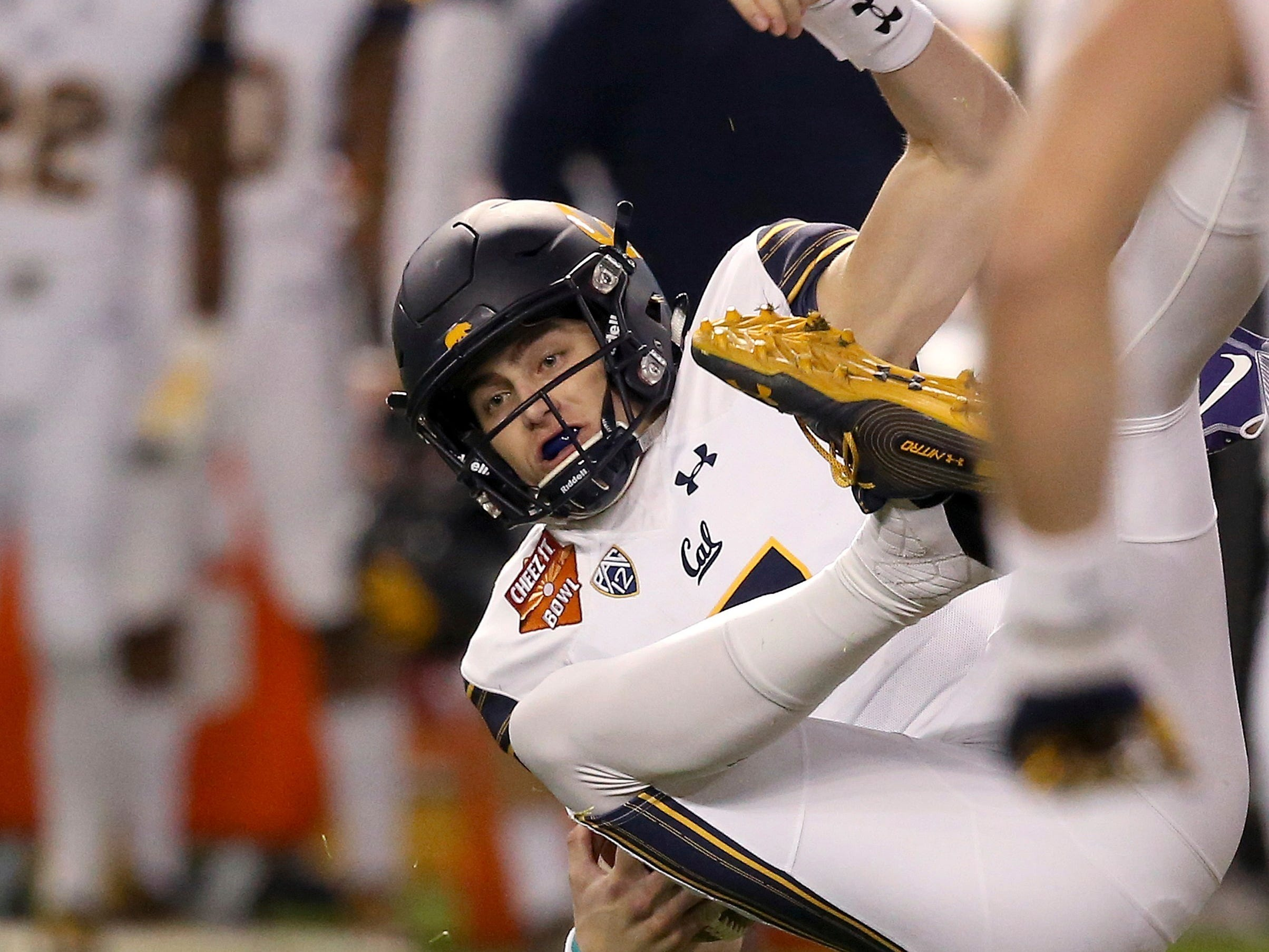 California quarterback Chase Garbers, top, gets upended by TCU safety Vernon Scott (26) during the first half of the Cheez-It Bowl NCAA college football game Wednesday, Dec. 26, 2018, in Phoenix.