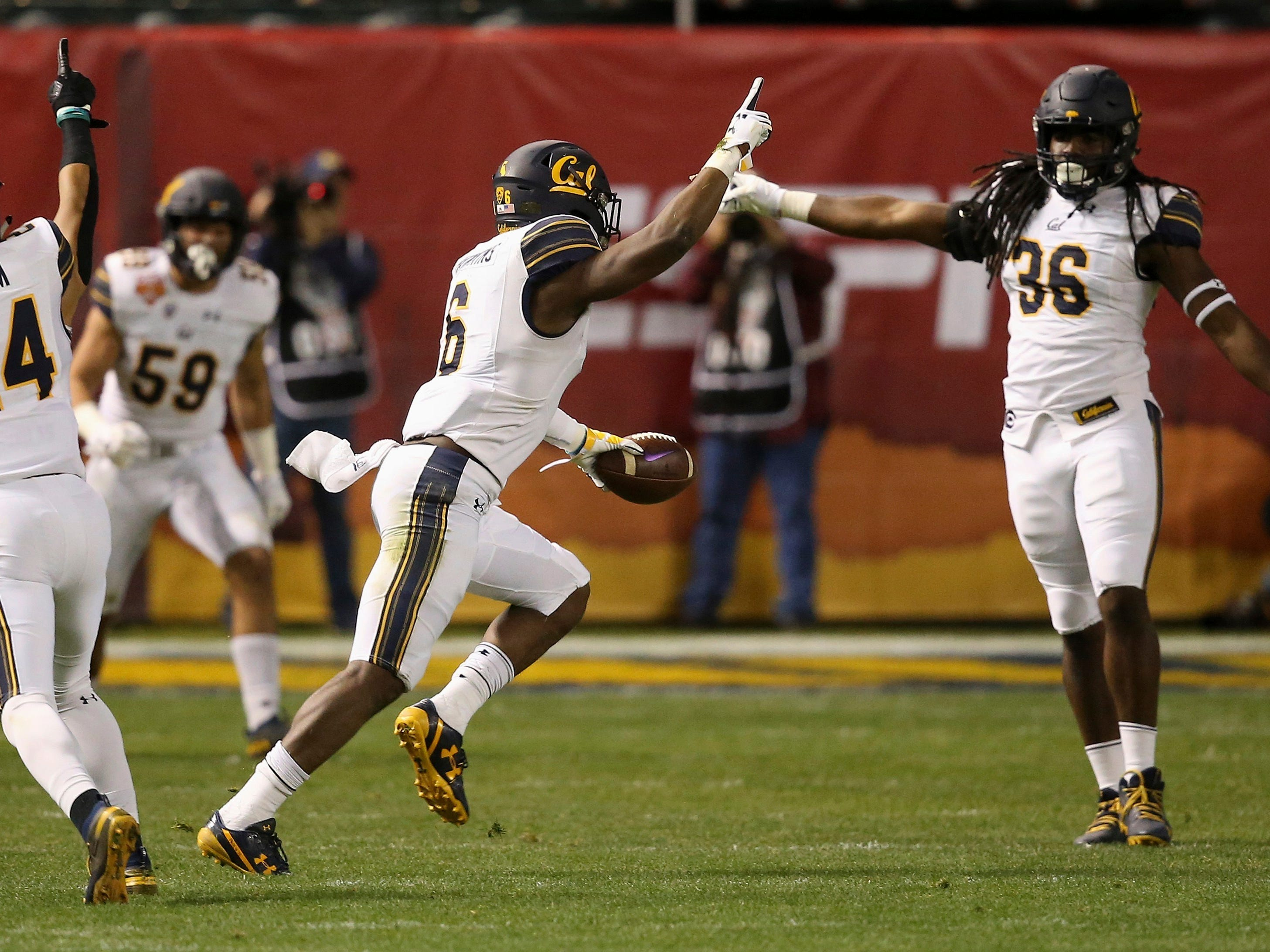 California safety Jaylinn Hawkins (6) celebrates his interception against TCU with linebacker Alex Funches (36) and cornerback Camryn Bynum (24) as linebacker Jordan Kunaszyk (59) watches during the first half of the Cheez-It Bowl NCAA college football game Wednesday, Dec. 26, 2018, in Phoenix.