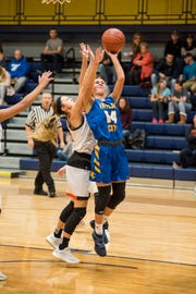 Marine City High School forward Kennedy Osterland attempts to block a shot by Imlay City High School forward Mary Lengemann (14) during their SC4 Holiday Basketball Showcase game Thursday, Dec. 27, 2018 at the SC4 Fieldhouse.