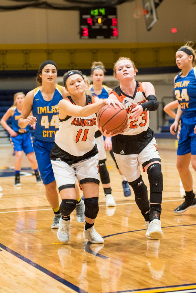 Marine City High School forward Kennedy Osterland (11) and guard Morgan McConnell reach for a rebound during their SC4 Holiday Basketball Showcase game against Imlay City High School Thursday, Dec. 27, 2018 at the SC4 Fieldhouse.
