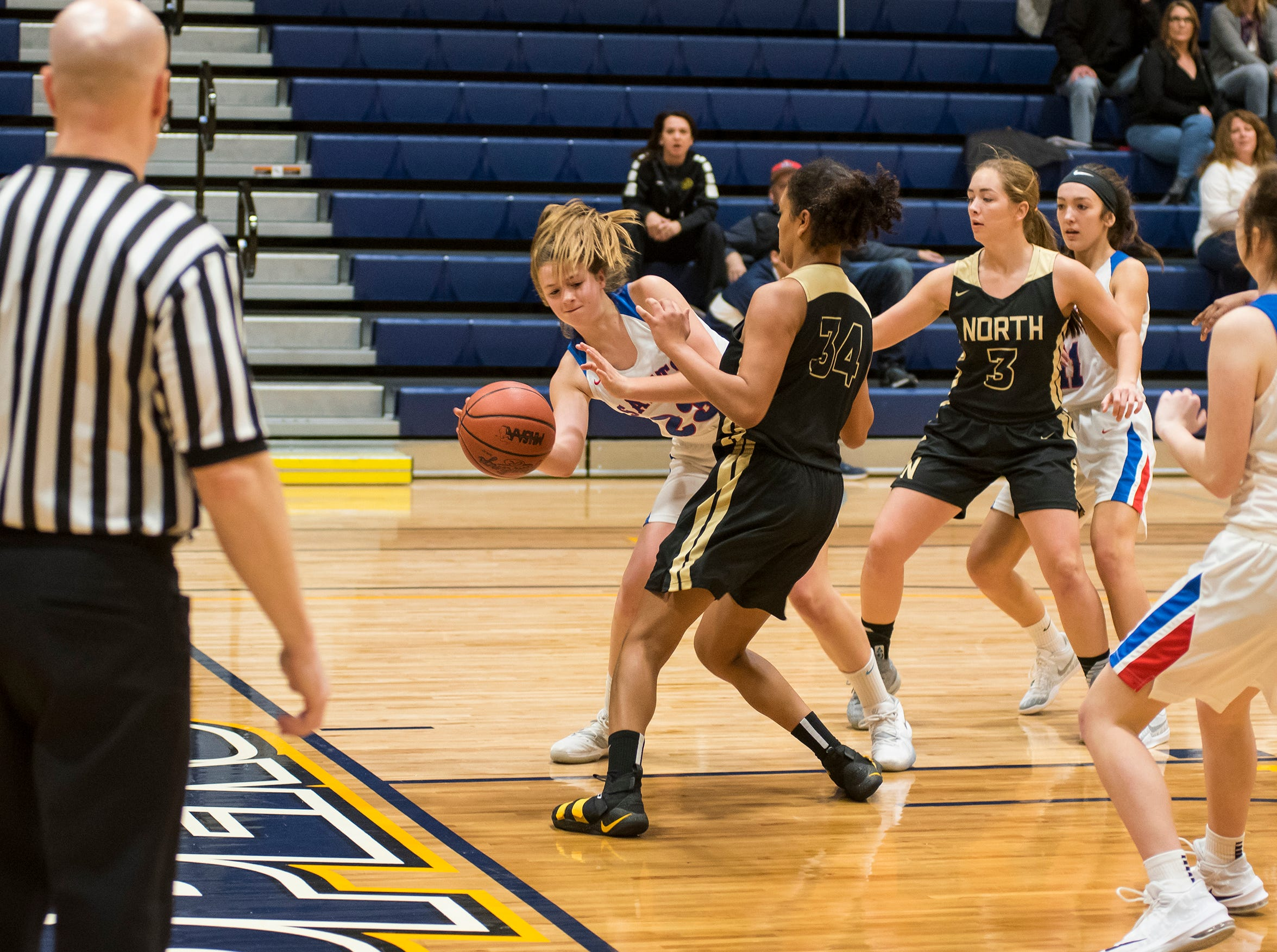 St. CLair High School forward Annaliese Lamontagne (23) passes the ball past L'Anse Creuse North High School forward Sapphire Conway during their SC4 Holiday Basketball Showcase game Thursday, Dec. 27, 2018 at the SC4 Fieldhouse.