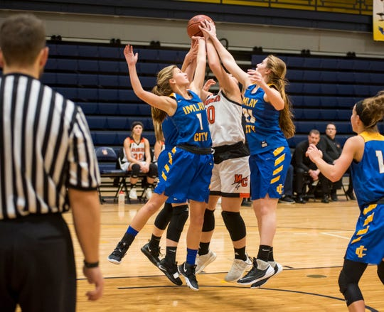 Imlay City High School guard Ana Lengemann (1) and forward Kayla Rossenn (21) reach over Marine City High School forward Katelynn MacEwan for a rebound during their SC4 Holiday Basketball Showcase game Thursday, Dec. 27, 2018 at the SC4 Fieldhouse.