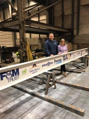 This steel beam, provided by Strait Steel and featuring decals from FastSigns, will be raised to celebrate 2019 at Greencastle-Antrim Education Foundation's Raising the Bar event, 6:30 to 8 p.m. Dec. 31, 2018, at Kaley Field. Pictured are Dallas Strait of Strait Steel and Cindy Marconi of GAEF.