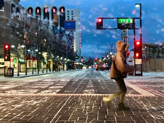 A woman crosses East Second Street as a light dusting of snow falls over downtown Reno on Dec. 27, 2018.