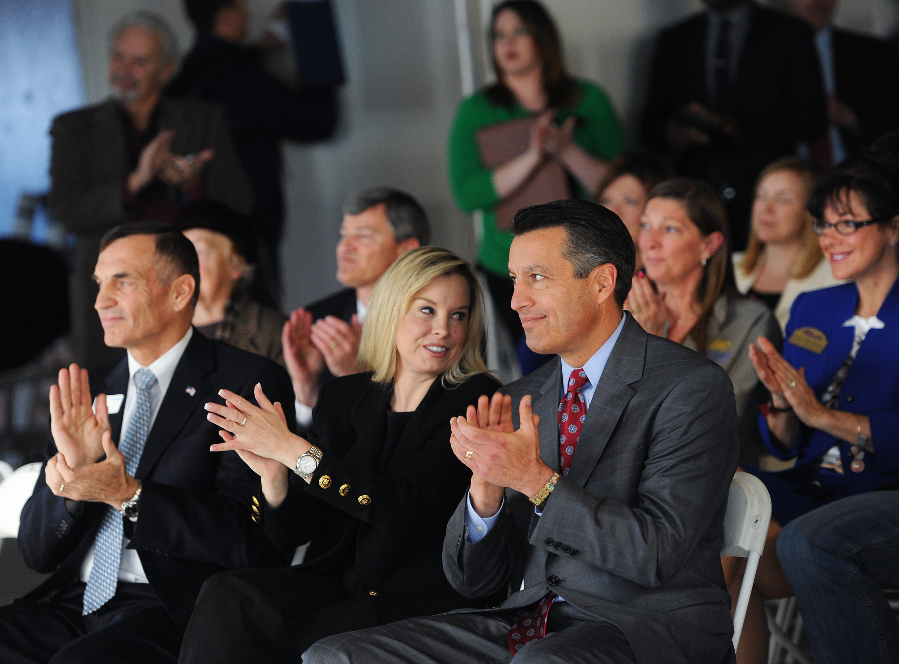 Reno Mayor Hillary Schieve, middle, and Nevada Governor Brian Sandoval applaud during an EDAWN press conference announcing Clear Capital's move from Truckee to downtown Reno at Park Center Tower on Jan. 6, 2015. EDAWN President and CEO Mike Kazmierski is seen on the left.