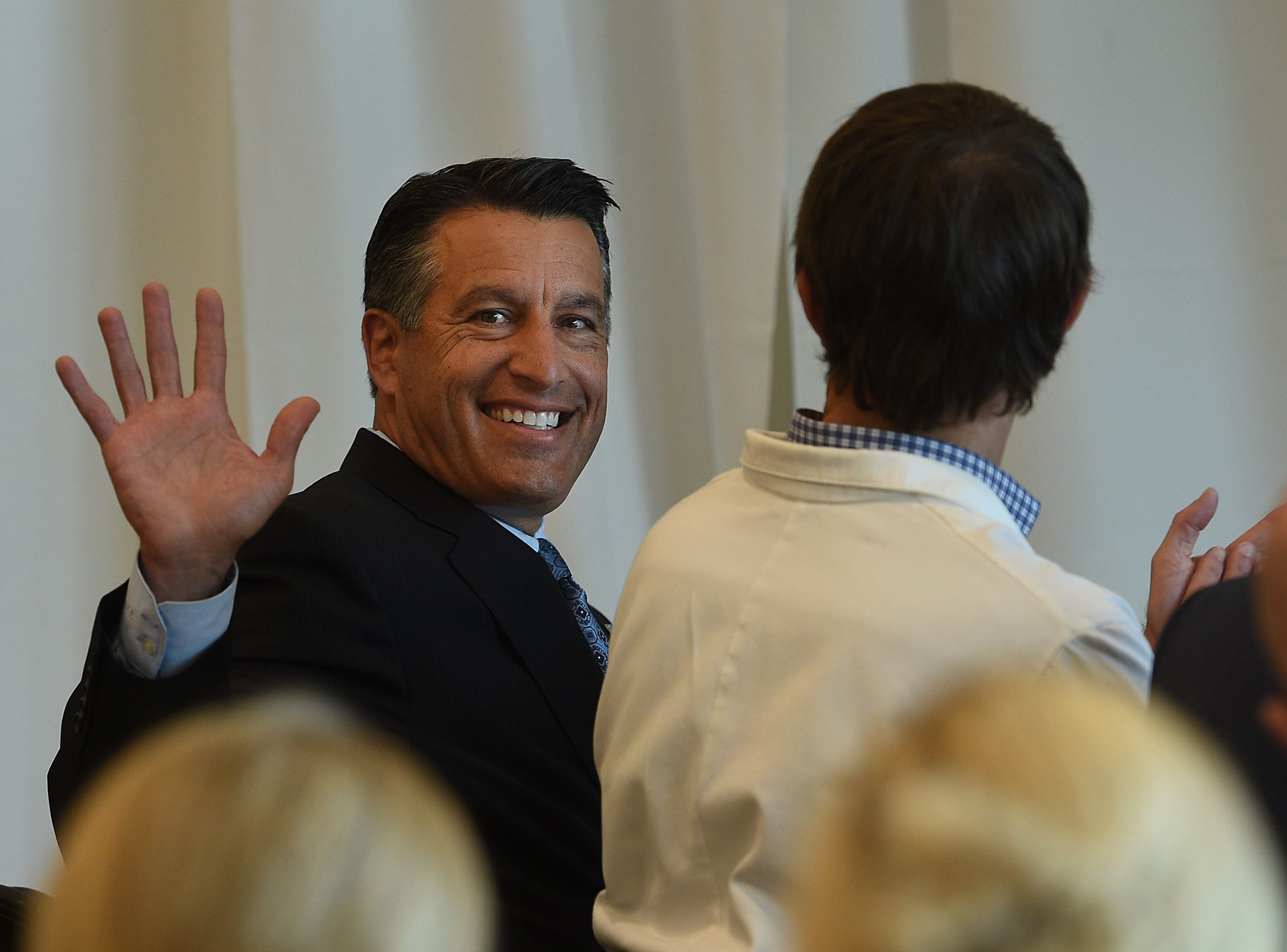 Nevada Governor Brian Sandoval waves to the crowd during the EDAWN press conference announcing the arrival of Grand Rounds, a medical technology company, to the Reno Tahoe Tech Center in Reno on May 13, 2015.