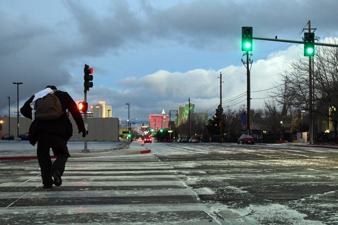 A man hurries to cross the intersection of Kuenzli and Sutro streets as a light dusting of snow falls in Reno on the morning of Thursday Dec. 27, 2018.