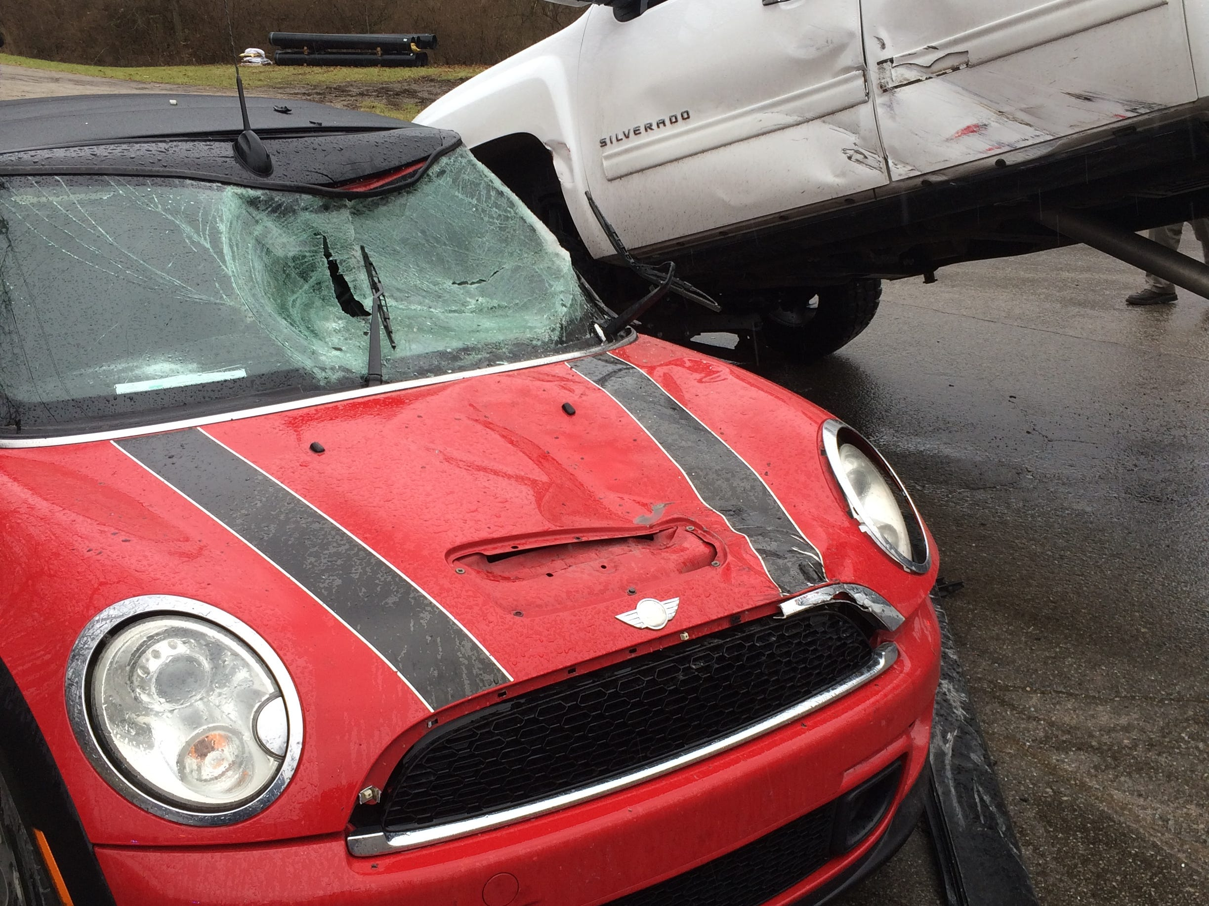 The removal of a Chevrolet Silverado pickup from atop a Mini Cooper reveals the damage to the Mini Cooper after a Thursday accident.