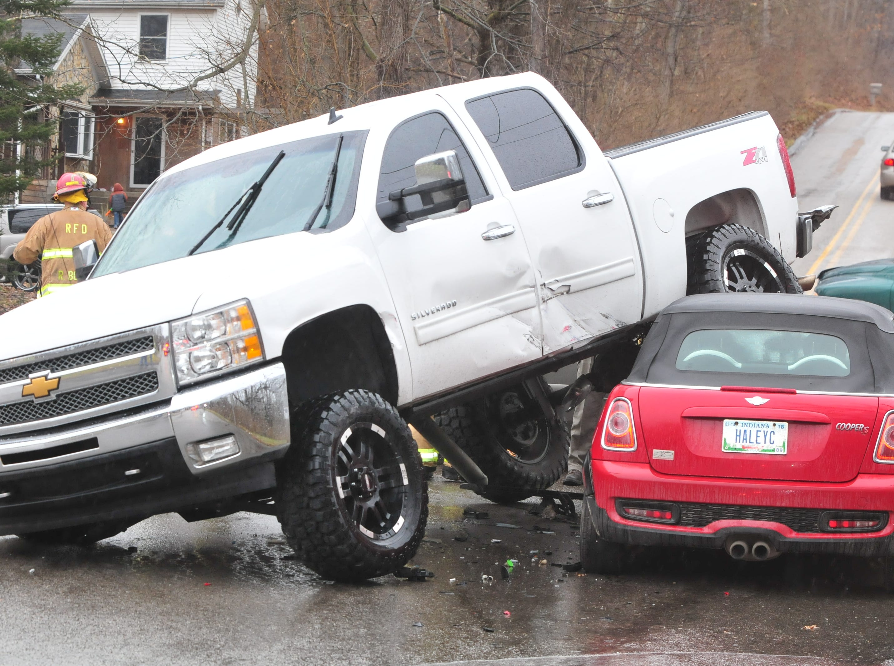 A Chevrolet Silverado pickup rests on a Mini Cooper after a three-vehicle accident Thursday on Indiana 121 at Hayes Arboretum Road.