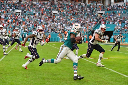 Miami Dolphins running back Kenyan Drake scores on the final play of the game to defeat the Patriots.