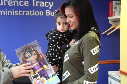 Nishka Marrero, 35, of Rochester, shows her daughter Victoria, 2, one of the many gifts collected by the Rochester Police Department and Latino Advancement in Public Safety (LAPS) Toy Drive on December 20 at Ibero. In December 2017 Marrero and her daughter moved to Rochester after being displaced from their home in Puerto Rico by Hurricane Maria.