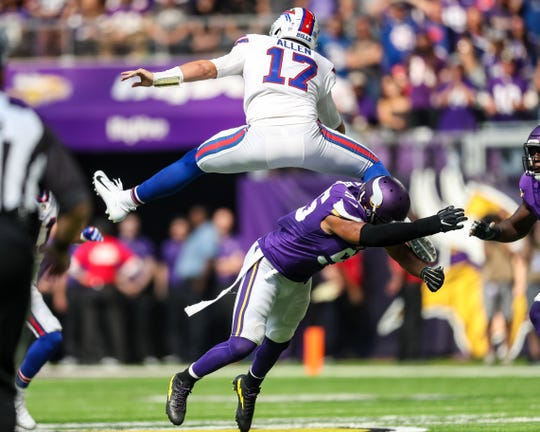 Buffalo Bills quarterback Josh Allen (17) hurdles Minnesota Vikings linebacker Anthony Barr (55) .