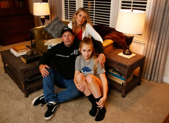 FILE - In this Nov. 26, 2018 file photo Jason James Burnett, accompanied by his daughter Faith and wife, Heather, poses at his mother-in-law's home in Chico, Calif. Burnett who lost her home in California's most destructive wildfire ever says she and her husband are humbled to have received pardons from Gov. Jerry Brown for old drug crimes. Burnett said Tuesday, Dec. 25, 2018, the pardons were bright spots in what has been a difficult period. Brown on Monday wiped away her conviction for possessing ephedrine with intent to make methamphetamine nearly 20 years after she was sentenced for the crime.