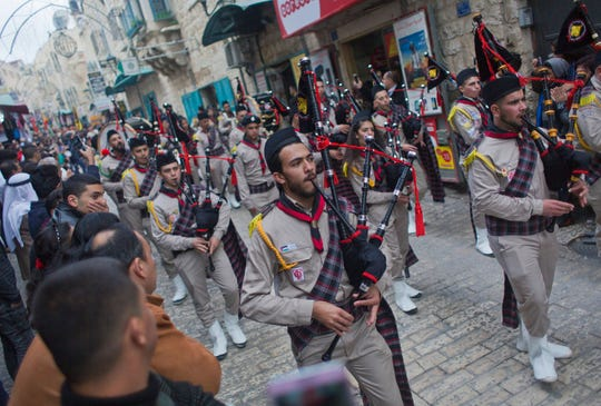 Palestinian scouts march through town ahead of midnight Mass at the Church of the Nativity, traditionally recognized by Christians to be the birthplace of Jesus Christ, in the West Bank city of Bethlehem, Monday, Dec. 24, 2018. Palestinians are preparing to host pilgrims from around the world in celebrating Christmas in the West Bank city of Bethlehem.