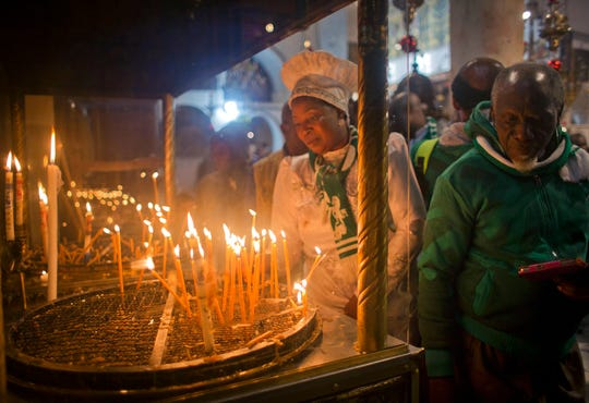 Christian worshippers light candles at the Church of the Nativity, traditionally recognized by Christians to be the birthplace of Jesus Christ, in the West Bank city of Bethlehem, Sunday, Dec. 23, 2018. Christians around the world will celebrate Christmas on Monday.