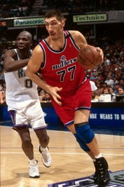 SACRAMENTO, CA - DECEMBER 16: Gheorghe Muresan #77 of the Washington Bullets dribbles the ball against the Sacramento Kings during a game played on December 16, 1996 at Arco Arena in Sacramento, California. NOTE TO USER: User expressly acknowledges and agrees that, by downloading and or using this photograph, User is consenting to the terms and conditions of the Getty Images License Agreement. Mandatory Copyright Notice: Copyright 1996 NBAE (Photo by Rocky Widner/NBAE via Getty Images)