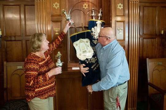 Lisa Priddle places crowns on the Torah scroll as her husband, Kenny Priddle, holds it at the Jewish synagogue in Dothan, Ala.