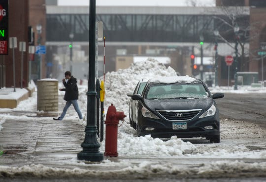 Slushy snow is piled up behind parked cars Thursday, Dec. 27, in St. Cloud.