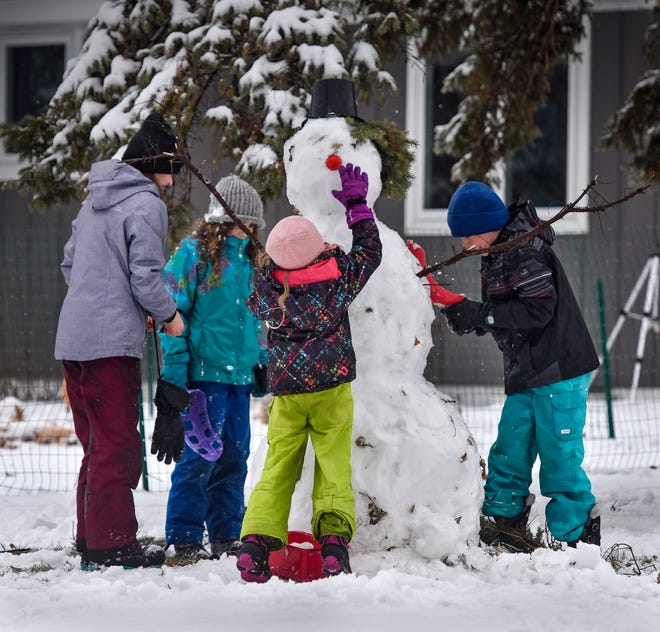 A bright red nose adds a festive touch to a snowman under construction by children after a fresh snowfall Thursday, Dec. 27, in St. Cloud.