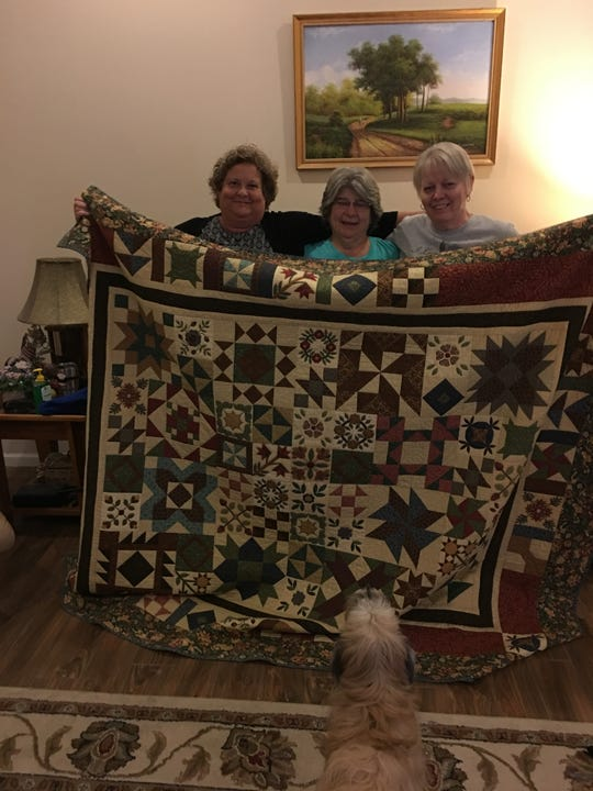 (From left to right) Quilt Blessings for the Panhandle founders Paula Cox, Teresa Stonecypher and Donna Miller stand with a quilt that was taken to areas hit hard by Hurricane Michael.