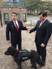 Jack Capra, Executive Officer and General Counsel for Northwest Florida State College with his service dog, 7 year old Labradoodle Rocco showing his Purple Heart to Sean White, Director of Legislative Affairs, Florida College System.