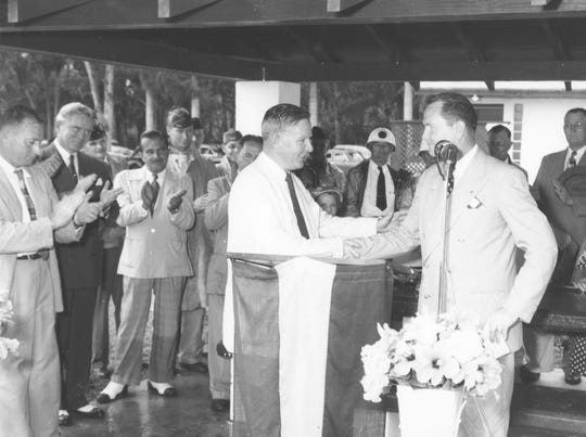 Two gentleman shake hands in front of a crowd during the MacWilliam Park and Charles Mitchell Highway dedication ceremony on May 30, 1952. Included in picture are Gov. Fuller Warren, Lou Berger, W. D. Graves, Charles Heath, and Merrill Barber.