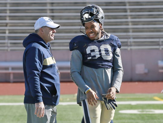 Pitt running back Qadree Ollison jokes with head coach Pat Narduzzi before their practice Thursday at the SAC.