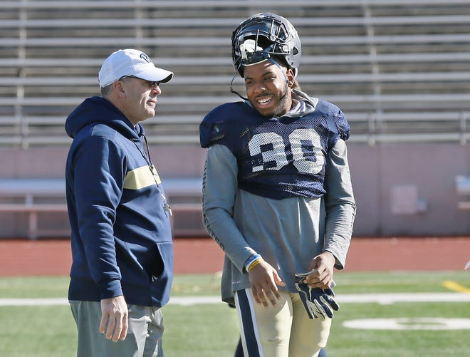 Pitt running back Qadree Ollison jokes with head coach Pat Narduzzi before their practice Thursday at the Socorro Student Activities Complex.