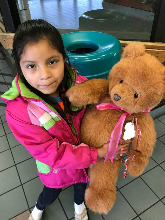 Guatemalan child Juana Marisol Tomas, 8, received a brand new jacket, clothes, slippers and a teddy bear from a shelter in El Paso before she boarded a bus with her mother to meet up with her father in Birmingham, Alabama.