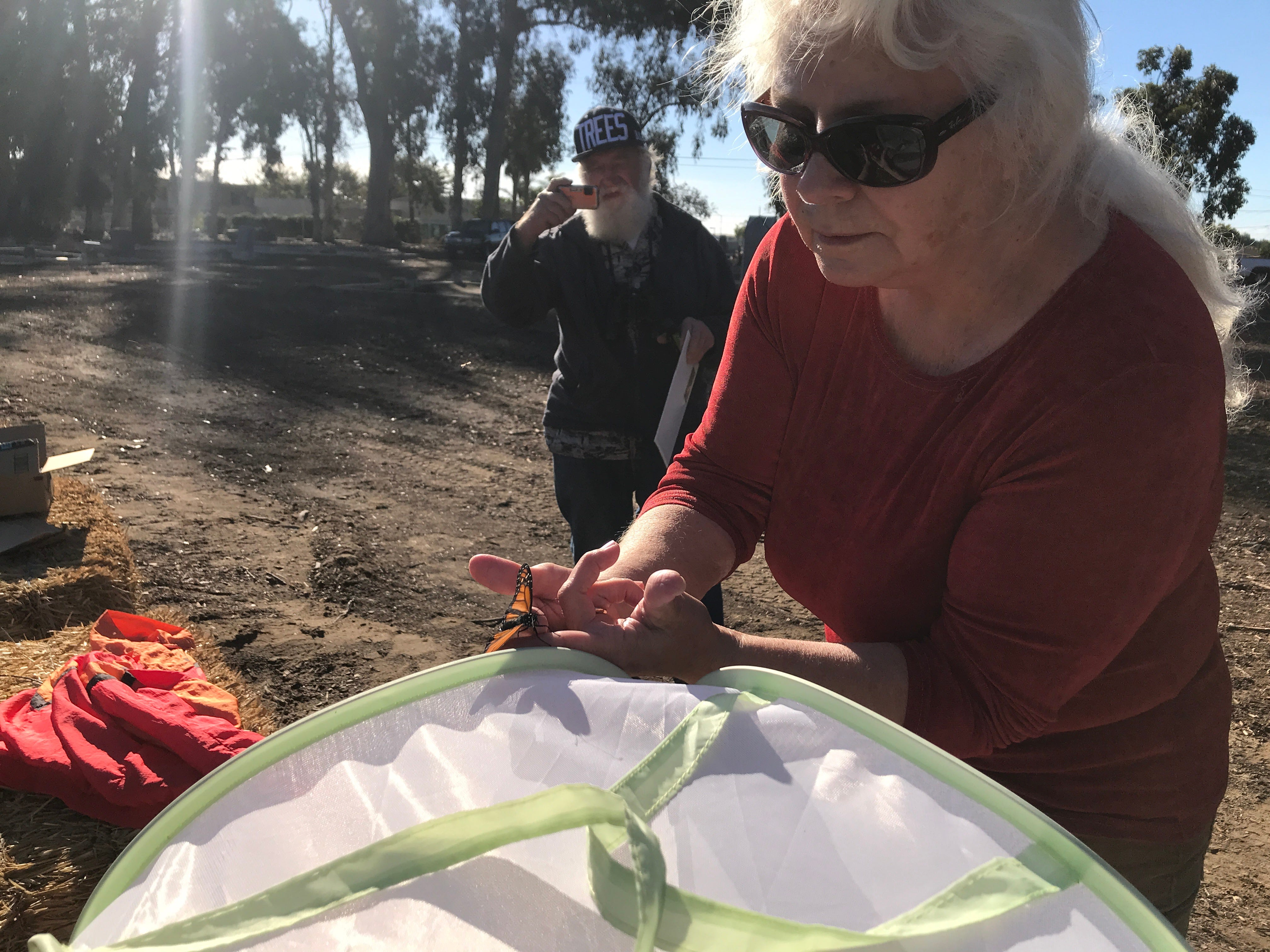 Nancy Cozza, president of the Huenemean Bohemian Artist Melting Pot Ministry, gets ready to release a monarch butterfly at the historic cemetery in Oxnard.