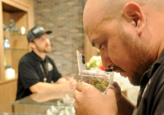 Francisco Martinez smells a sample of marijuana before buying at Safe Port Cannabis Dispensary in Port Hueneme. Neighboring Oxnard will soon have eight dispensaries.